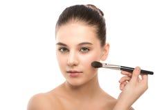 有干净的面孔的年轻深色的妇女 应用化妆刷子的女孩完善的皮肤 笤帚查出的白色 库存照片