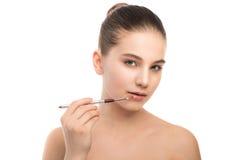 有干净的面孔的年轻深色的妇女 应用化妆刷子的女孩完善的皮肤 笤帚查出的白色 免版税库存图片