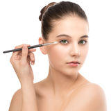 有干净的面孔的年轻深色的妇女 应用化妆刷子的女孩完善的皮肤 笤帚查出的白色 免版税库存照片