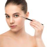有干净的面孔的年轻深色的妇女 应用化妆刷子的女孩完善的皮肤 笤帚查出的白色 免版税图库摄影