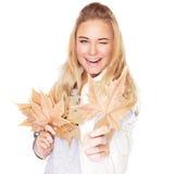 有干燥叶子的快乐的女孩 免版税库存图片