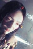 有干燥玫瑰的女孩在湿玻璃后 免版税库存图片