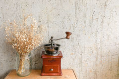 有干燥花的咖啡手磨床对有拷贝空间的艺术墙壁 库存照片
