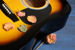有干玫瑰的声学吉他在木桌上 给的歌手记忆做广告音乐会模板  免版税图库摄影