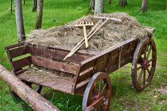 有干草和犁耙的村庄无盖货车 免版税库存照片