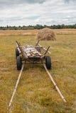 有干草的老推车在以树为背景的领域 免版税库存图片