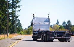 有平床拖车的大船具半卡车起动路与树 免版税库存照片