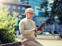 有平板电脑的老人在城市街道上 免版税库存照片