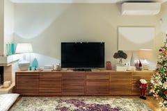 有平的电视的当代木客厅内阁 库存照片
