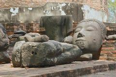 有平静的expresssion的古老打破的菩萨头和其他石头 免版税库存照片
