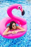 有年轻和性感的女孩谎言在阳光下与鸡尾酒杯的一个可膨胀的巨型桃红色火鸟水池浮游物床垫 有吸引力的 免版税库存照片