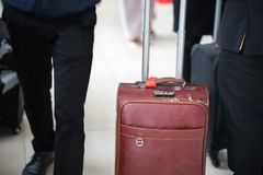 有年轻商人的旅行皮革行李在一个现代时髦的衣服特写镜头在机场 免版税图库摄影