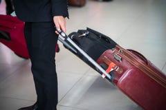 有年轻商人的旅行皮革行李在一个现代时髦的衣服特写镜头在机场 图库摄影