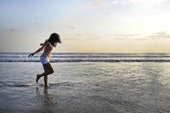 有年轻愉快和激动的亚裔的妇女乐趣享用嬉戏和释放在日落海滩在旅游业假期 库存照片