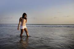 有年轻愉快和激动的亚裔的妇女乐趣享用嬉戏和释放在日落海滩在旅游业假期 免版税库存照片