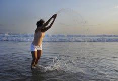 有年轻愉快和激动的亚裔的妇女乐趣享用嬉戏和释放在日落海滩在旅游业假期 免版税图库摄影