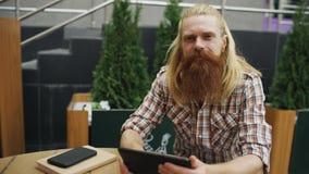 有年轻有胡子的人画象有坐在咖啡馆的片剂计算机的户外微笑和放松和其余工作 库存照片