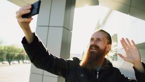 有年轻有胡子的行家的人与智能手机照相机的网上录影闲谈,当旅行城市街道时 免版税库存照片