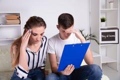 有年轻白种人的家庭债务问题,不能付出他们的贷款 玻璃和深色人学习的女性 免版税库存图片