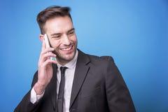 有年轻的商人在他的电话的一次快乐的交谈 免版税图库摄影