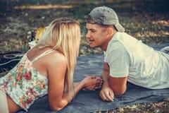 有年轻的夫妇说谎在看彼此的草坪的毯子的野餐 库存照片