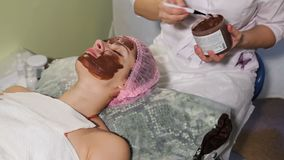 有年轻美丽的妇女在她的面孔的温泉做法 巧克力温泉 巧克力套 特写镜头 影视素材