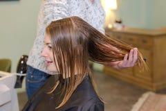 有年轻美丽的妇女头发被剪在美发师 免版税图库摄影
