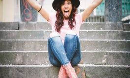 有年轻行家的妇女乐趣投掷的五彩纸屑用她的手-庆祝她的gratuation的愉快的俏丽的女孩坐台阶 免版税图库摄影