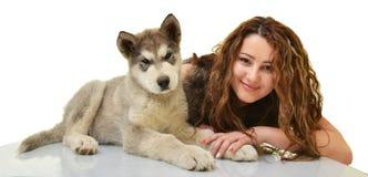 有幼小狗阿拉斯加的爱斯基摩狗的美丽的妇女 免版税图库摄影