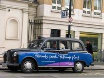 有广告横幅的传统伦敦出租汽车停放了在小室等级 库存照片