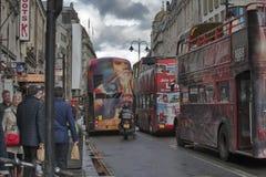 有广告的双层公共汽车在以风雨如磐的天空为背景的边 在工作家以后的人仓促 库存图片