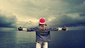 有广泛间隔的胳膊的一个十几岁的女孩 牛仔布衣物 棒球帽 以海和美丽的云彩为背景 的treadled 库存照片