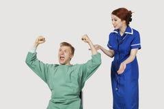 有庆祝成功的女性护士的年轻男性患者反对灰色背景 库存图片