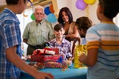 有庆祝生日聚会的家庭和朋友的男孩 免版税图库摄影
