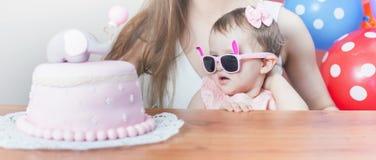 有庆祝第一个生日的滑稽的婴孩的母亲 蛋糕 库存照片