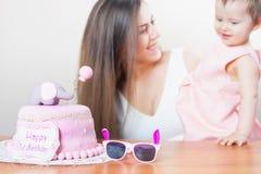 有庆祝第一个生日的滑稽的婴孩的母亲 蛋糕 免版税图库摄影