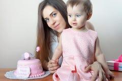 有庆祝第一个生日的滑稽的婴孩的母亲 蛋糕 库存图片