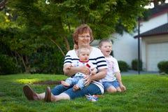 有庆祝7月4日的两个小男孩的愉快的祖母 免版税库存照片