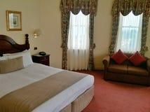 有床和沙发的旅馆客房 免版税库存图片