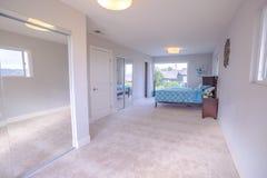 有床的宽敞长的主卧室 免版税图库摄影