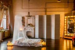 有床的,机盖,与花的布置的一个白色壁炉,一个白色屏幕,一个大镜子顶楼式室和点燃能 免版税库存照片
