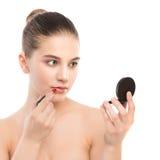 有应用唇膏的完善的干净的面孔的年轻深色的妇女使用镜子 笤帚查出的白色 免版税库存照片