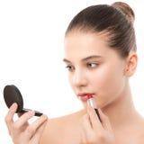 有应用唇膏的完善的干净的面孔的年轻深色的妇女使用镜子 笤帚查出的白色 库存照片