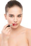 有应用唇膏的完善的干净的面孔的年轻深色的妇女 笤帚查出的白色 库存照片