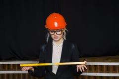 有应用排的美丽的白肤金发的女实业家在橙色建筑盔甲和衣服的顶楼办公室 库存图片