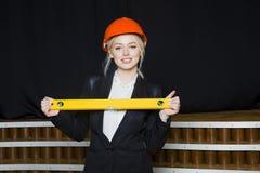 有应用排的美丽的白肤金发的女实业家在橙色建筑盔甲和衣服的顶楼办公室 图库摄影