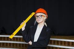 有应用排的美丽的白肤金发的女实业家在橙色建筑盔甲和衣服的顶楼办公室 库存照片