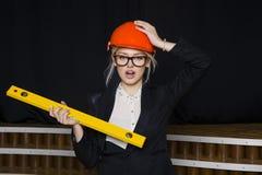 有应用排的美丽的白肤金发的女实业家在橙色建筑盔甲和衣服的顶楼办公室 免版税库存图片