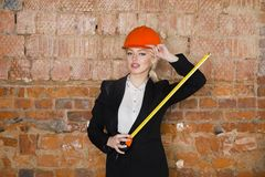 有应用排的美丽的白肤金发的女实业家在橙色建筑盔甲和衣服的顶楼办公室 免版税库存照片
