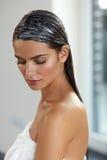 有应用的自然头发面具的年轻美丽的妇女 护发 图库摄影